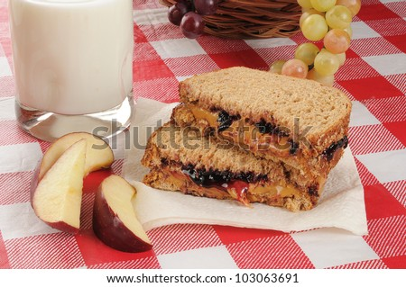 A peanut butter and jelly sandwich with apple slices and milk