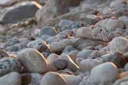 A pebble beach. The light dwindles to sunset. Soft shadows add feel to rounded pebbles. Light catches the pebbles to one side and accentuates their shape. Neutral, warm tones. Abstract nature image.