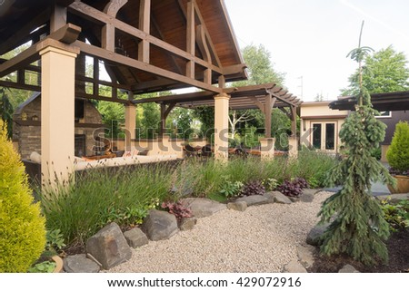 A Pebble Pathway Winds Past A Custom Designed Backyard Patio Shelter.