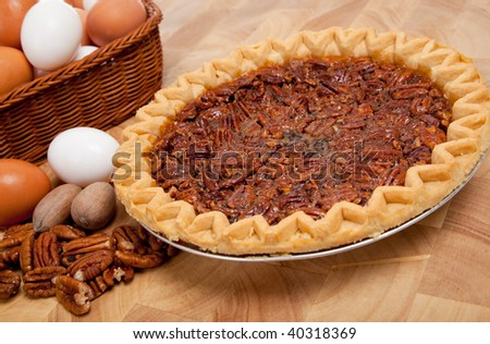 A pecan pie on cutting board with ingredients including pecans and eggs
