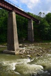A pedestrian bridge with a railing rises above the turbulent mountain river on long concrete columns