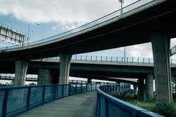 A pedestrian bridge with blue fences under two concrete bridges with columns under a cloudy sky