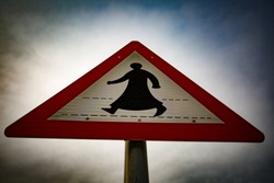 A pedestrian crossing sign featuring a robed figure.