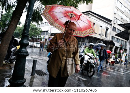 A pedestrian protect herself from the rain with umbrellas during a rainfall in Athens, Greece on Oct. 11, 2016