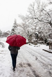 A pedestrian walking in the snow with a red umbrella at Shirakawa village in Japan, a UNESCO world heritage site.