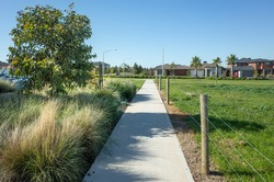 A pedestrian walkway/footpath leads to a residential neighbourhood with some modern Australian homes. Suburban view over a park with houses in the distance. Melbourne VIC Australia.