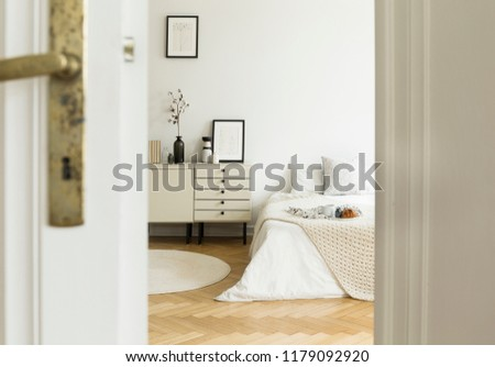 A peek through a half open door into a monochromatic beige and white bedroom interior with a bed and a drawer cabinet. Real photo. #1179092920