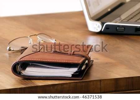 a pen an address book, glasses and laptop