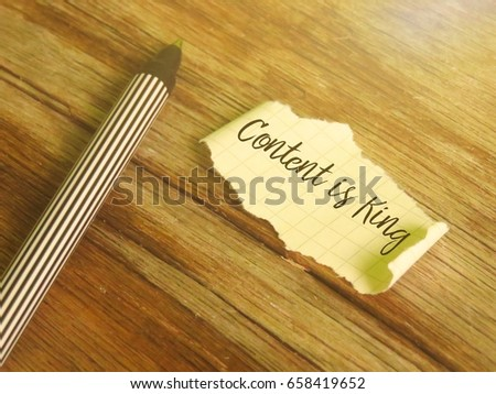 A pen and a piece of paper written 'Content is King' on wooden table. #658419652