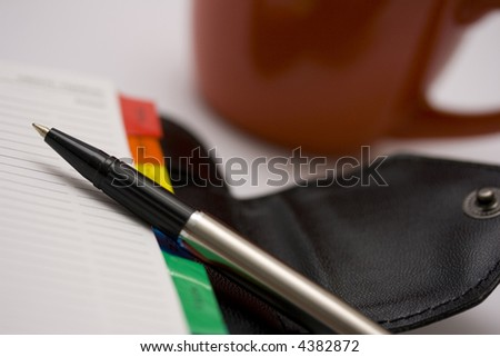 A pen and an organizer on a table with an red coffee mug on the background