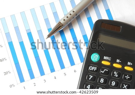 A pen and calculator on top of a business chart.