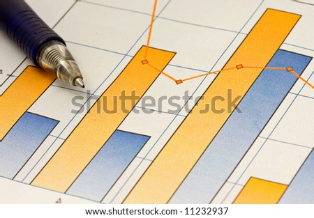 A pen composed over a business chart of earnings trends.