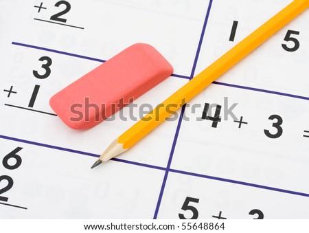 photo : A pencil and an eraser on a math sheet background, math homework