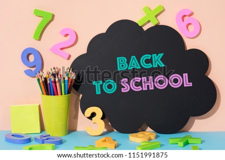 a pencil pot with pencil crayons of different colors, some three-dimensional numbers of different colors and the text back to school written in a black thought bubbles, against a pink background