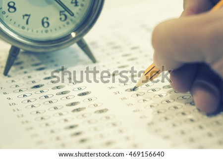 A pencil sitting on a test bubble sheet and alarm clock, optical form of an examination,Answer sheet with pencil,Standardized test form with answers bubbled and a black pencil,selective focus,vintage