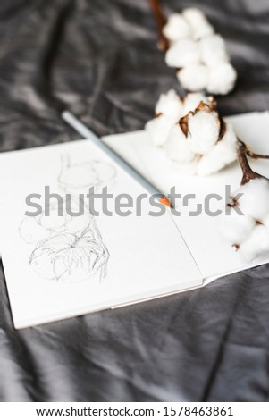 A pencil sketch of cotton. An open sketchbook lies on the bed. Hobbies and leisure.