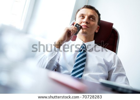 A pensive businessman sitting at table with a mobile phone
