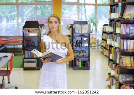 A pensive woman standing in the middle of the book room with a big book