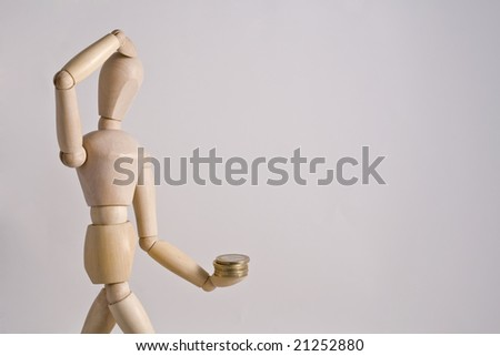 A pensive  wood toy with money in one of his hands