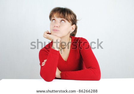 A pensive young woman in a red sweater at the desk, isolated on white