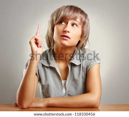 A pensive young woman sitting at the desk, isolated on grey