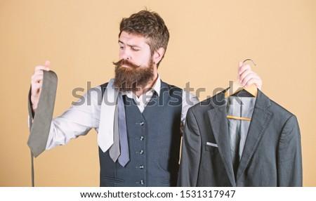 A perfect choice. Businessman choosing necktie, choice concept. Bearded man matching tie color to suit jacket in store. Hipster making shopping choice in shop. Choice of clothes and accessories. #1531317947