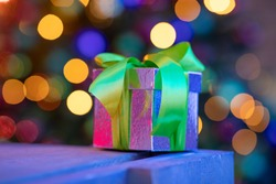 A perfect little christmas gifts onder a christmastree with lights in the background - Christmas presents under a tree