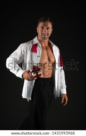 A perfect romantic gift for her. Handsome man holding gift on black background. Athletic guy with fit torso and gift box. Sexy macho showing muscular six pack abs and birthday or valentines gift.