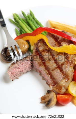 A perfectly cooked veal sirloin steak sliced open and served with mushrooms, capsicum ribbons, asparagus fries.