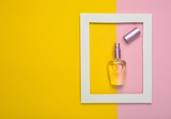 A perfume bottle in a white frame on a colored pastel background. Minimalist trend. Top view.