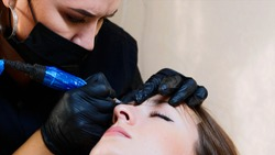 A permanent master in gloves and a mask is doing microblading for the brows of a young lady client at the beauty studio. The camera shows the half part of woman's face.