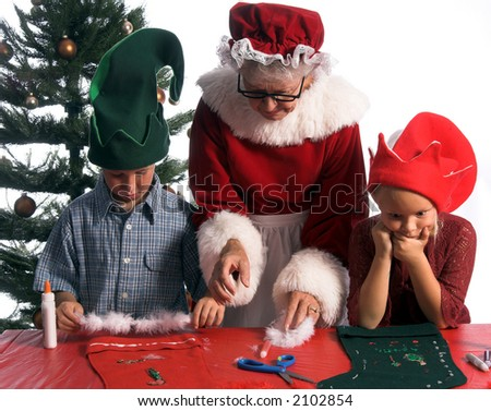 A perplexed young girl elf ponders her work while a boy and Mrs. Santa Claus continue working on a Christmas craft project of decorating a stocking