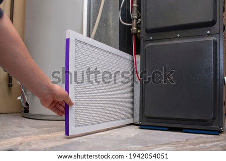 A person changing an clean air filter on a high efficiency furnace ストックフォト ©