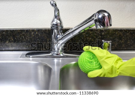 A person cleaning the kitchen sink with a glove