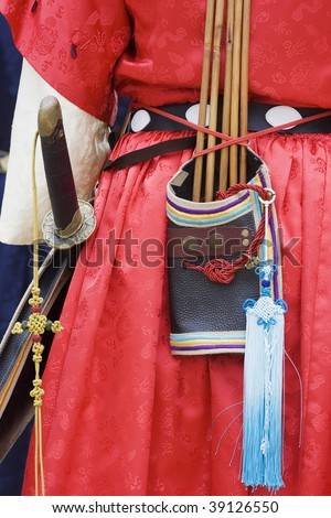 A person dressed in traditional oriental dress.  He's an archer/soldier as he has arrows and a sword. - stock photo