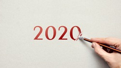 A person erases the number 2020 with an eraser. The new year is coming soon. Erasing the old life