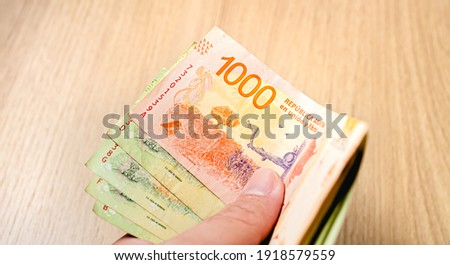 A person holding a group of banknotes of argentine pesos, the money of the argetine. Photo for representation of economy and finance. Photo stock ©