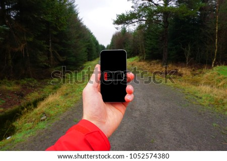 A person holding a phone in their hand with no signal. It is cold and wet and in the background a trail runs through coniferous forest.