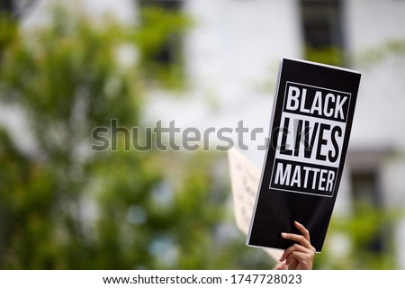 """A person holding a printed black sign """"black lives matter"""" at a racially oriented rally. A blurred building and trees in the background"""