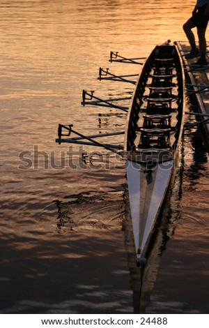 a person holding a row boat along the dock with their foot in the seattle sunrise