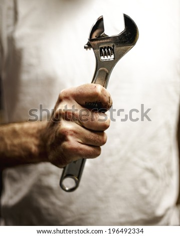 A person holding a wrench in their hand.