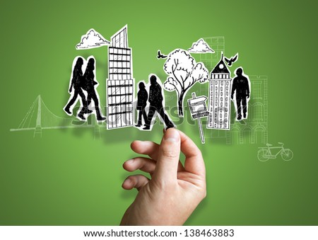 A person holding paper city elements.