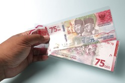 A person holds rupiah currency with a nominal value of 75,000 rupiah. To coincide with Indonesia's 75th Independence Day