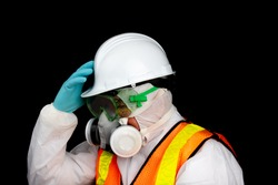 a person in a hazmat suit wearing an industrial respirator mask, hard hat and safety goggles isolated on black