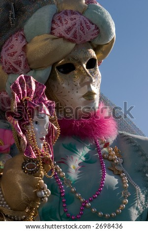 A person in a Venice carnival costume holding a mask