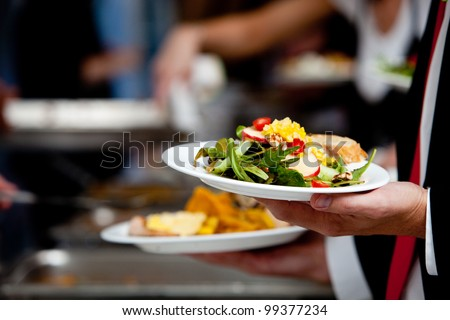 a person in line with their food during a banquet or other catered event