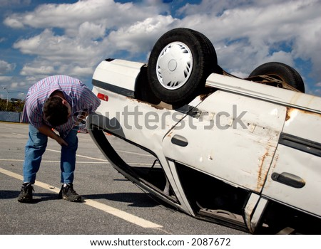 A person inspecting damage to an overturned car