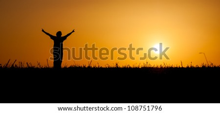 A person is celebrating life at a beautiful sunset or sunrise - stock photo