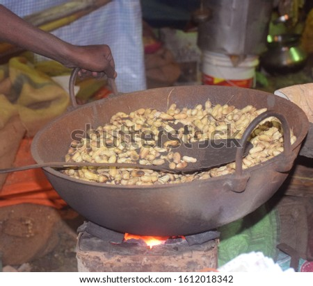 A person is roasting the groundnuts in West Bengal, India