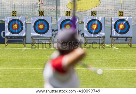 A person is shooting with recurve bow on a target during an archery competition. Focus on the targets.